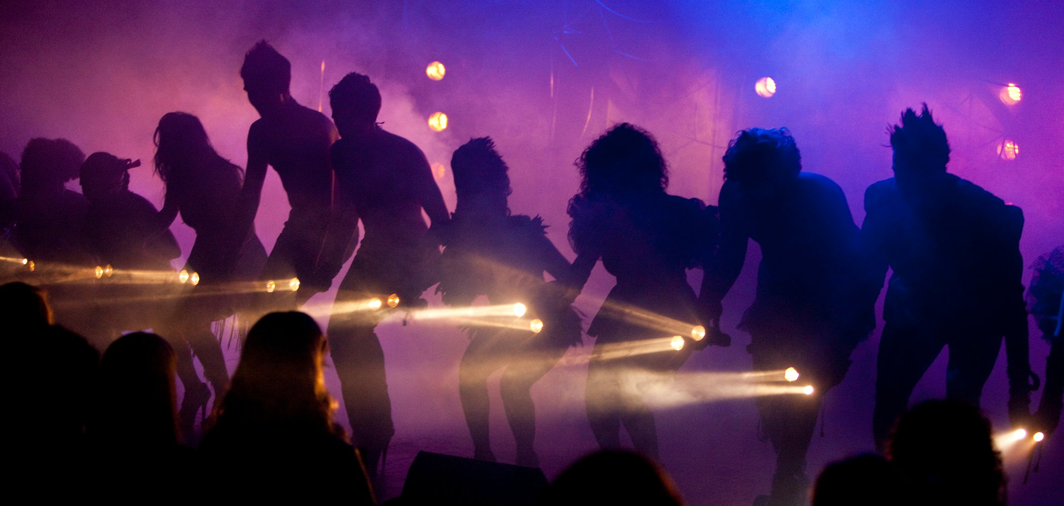 Performers on stage with dramatic lighting